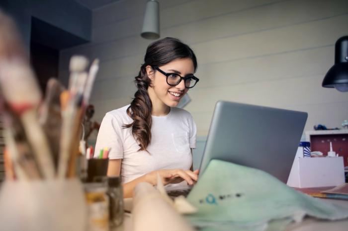 ein Mädchen mit Brillen ist erstaunt, wie praktisch es ist, mit Dropbox zu arbeiten