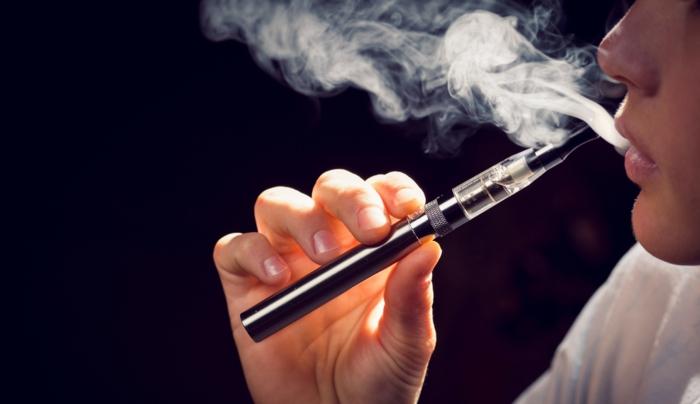 ein Junge raucht E-Zigarette, E-Zigaretten in schwarzer Farbe mit einer weißen T-Shirt