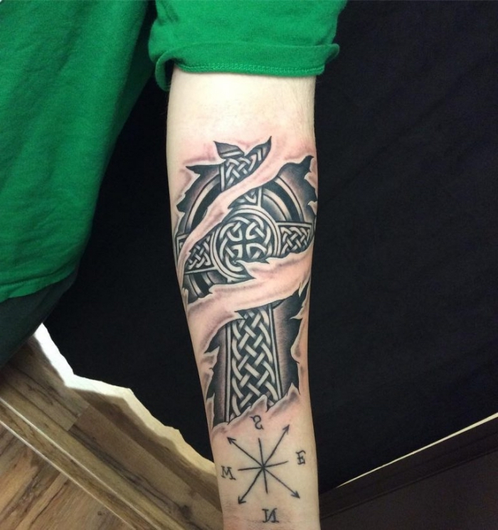 eisernes kreuz tattoo in schwarz und grau am arm, zerrissene haut, keltische motive, kompass am unterarm