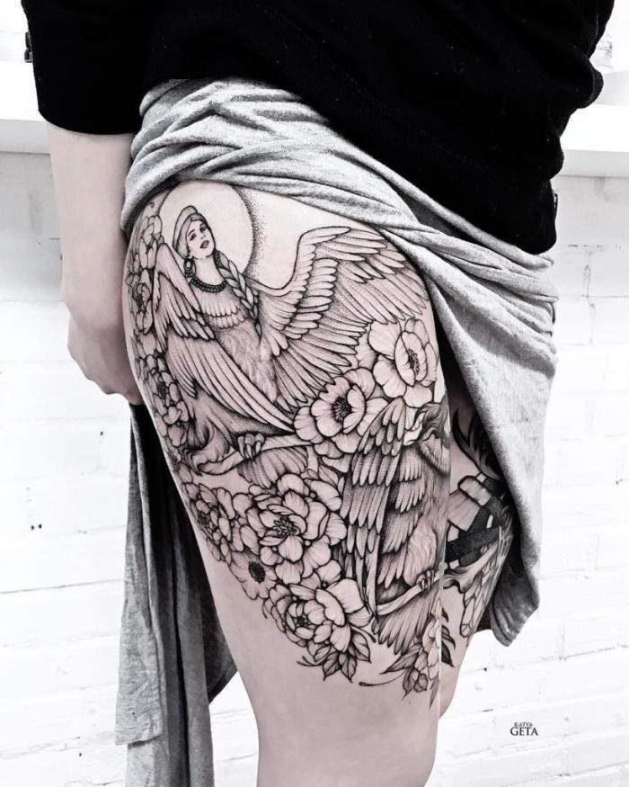 engelsflügel tattoo am oberschenkel, blackwork tätowierung, frau mit großen flügeln, florale motive, blumen