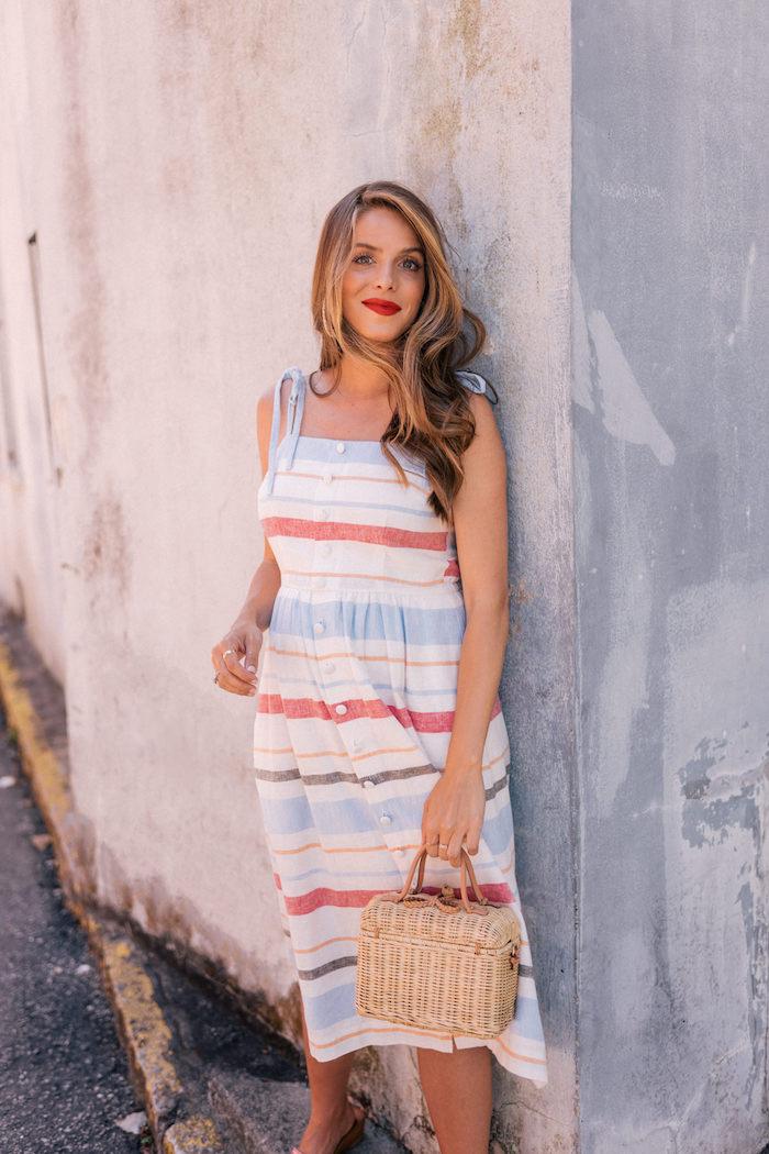 Elegantes Sommerkleid für den Alltag, gestreiftes Kleid in Pastellfarben mit Köpfen, mit dünnen Trägern, Rattan Tasche