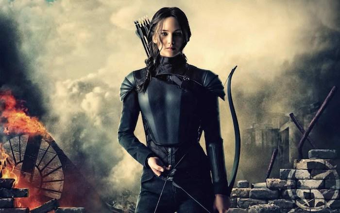 ein poster von dem hunger games film mit der schauspielerin jennifer lawrence mit einem schwarzen kostüm aus ledder und mit schwarzen pfeilen, die tribute von panem