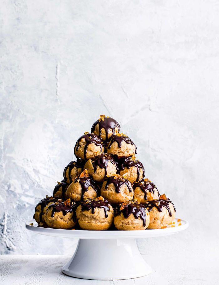 Turm aus Windbeuteln mit Schokolade auf Tortenständer, Fingerfood für Party
