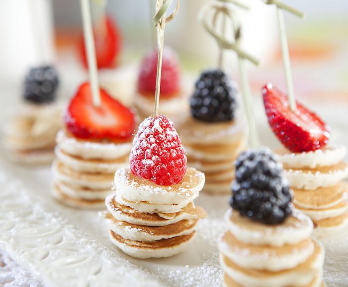 Mini Pfannkuchen mit Beeren und Puderzucker, kleine Häppchen für Party Gäste