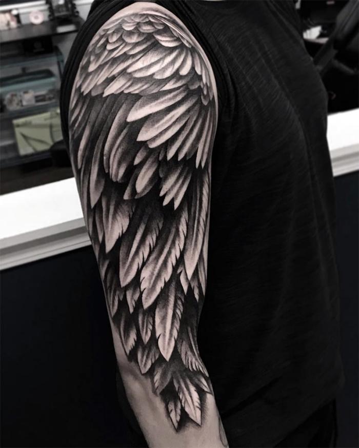 flügel tattoo ideen, mann mit großer blackwork tätoweirung am oberarm, tattoo am arm, viele feder