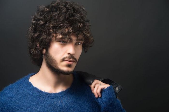 herren haarschnitt ideen für mann mit lockigen haaren, ein blauer pullover