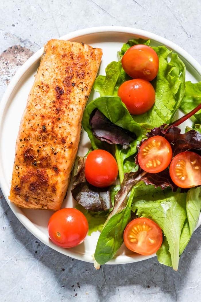 gerichte ohne kohlenhydrate, gebratener fisch mit salatblättern und cherry tomaten, low carb