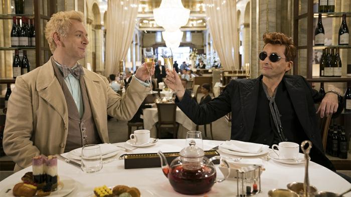 der Dämon und der Engel schenken ein Glas Sekt ein auf einem schönen gedeckten Tisch