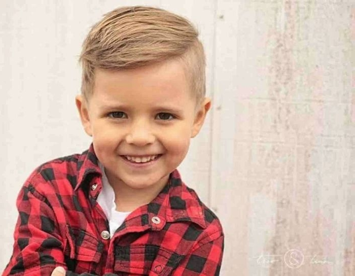 jungen haarschnitt schwarz rot kariertes hemd und ein nettes kind lächelt