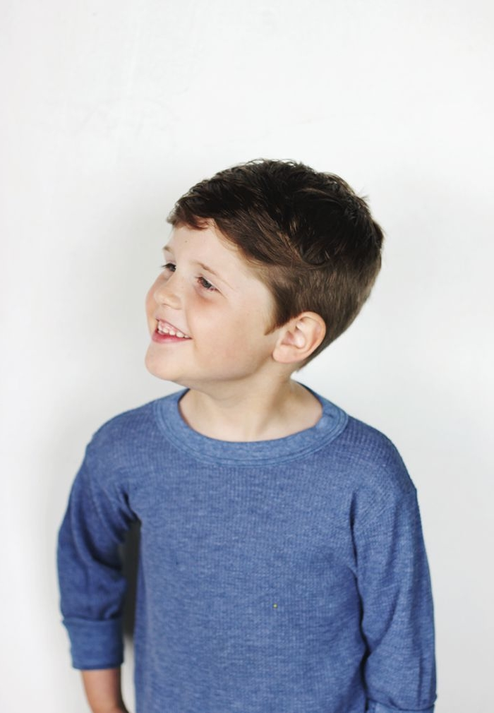 coole frisuren für jungen, ein junge mit dunkelbraunen haaren und blaue bluse