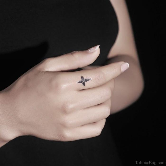 tätowierung mit kreuz als motiv, finger tattoo frau, französische nägel, kleines tattoo am zeigfinger