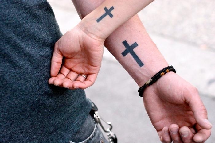 kleine tattoo motive für paare, mann und frau mit passenden tätowierungen an den ärmeln, schwarzes kreuz