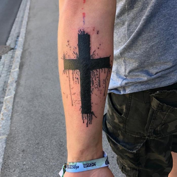 kreuz tattoo ideen, große blackwork tätowierung am unterarm, mann mit tattoo am arm