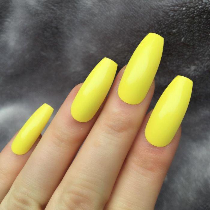 nägel spitz, gelbe nägel, lange schöne maniküre, finger einer frau foto
