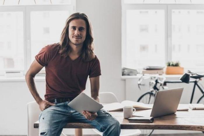 mittellange frisuren wachsen lassen bis sie so lang wie bei deisem mann werden, ein künstler sitzt auf dem tisch, laptop daneben