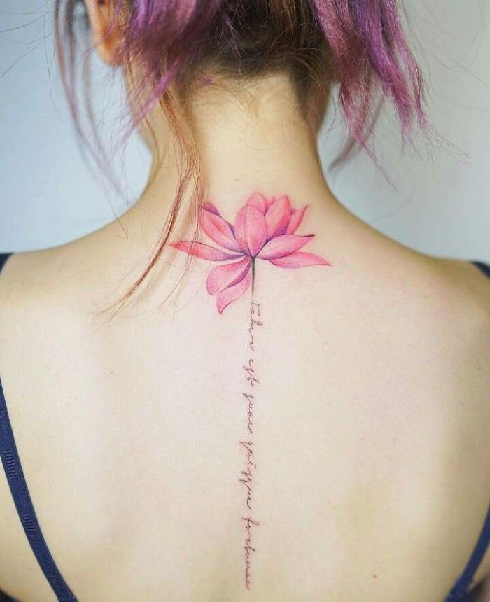 rosa lotusblute mit schriftzug, lotus tattoo am rücken, frau mit wasserfarben tätowierung