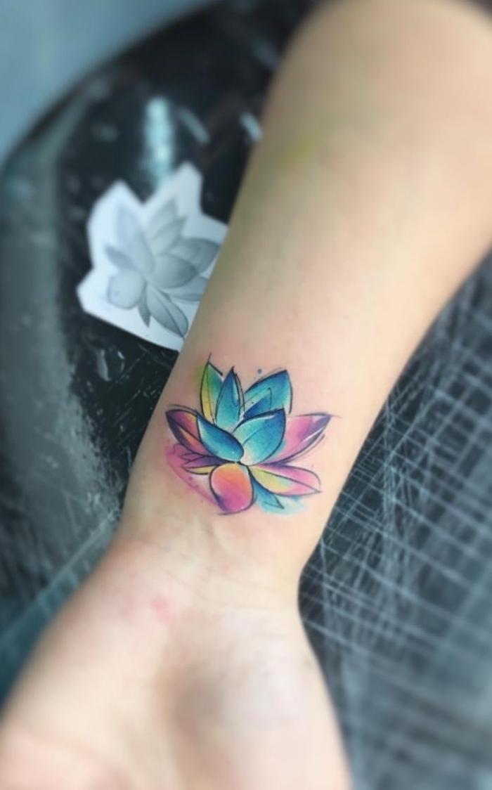 lotus tattoo am arm, kleine lotusblüte in blau, rosa und gelb, tattoo motive für frauen, blumen