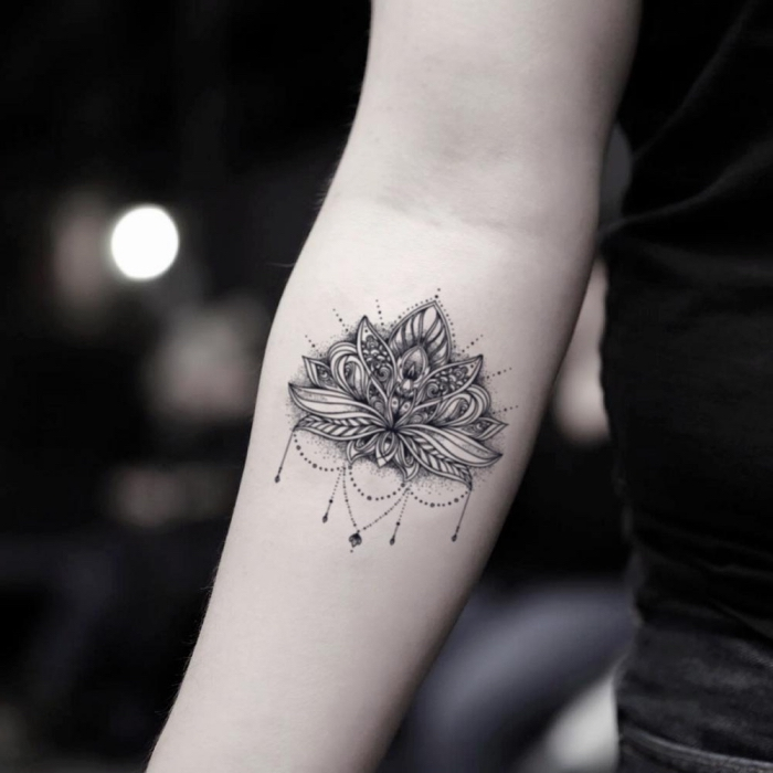 lotusblüte bedeutung, detailliertes tattoo am unterarm, schwarz graue tätowierung am arm