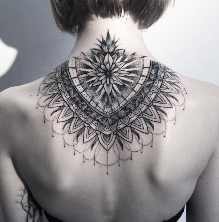 frau mit großem blackwork tattoo am rücken, lotusblüte bedeutung, geometrische elemente, mandala