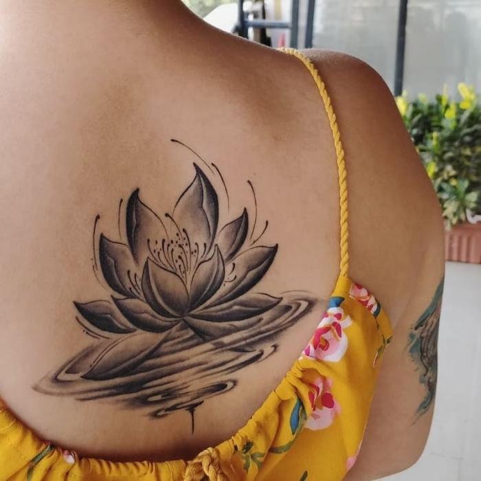lotusblüte bedeutung, lotus im wasser, große schwarz graue tätowierung am rücken