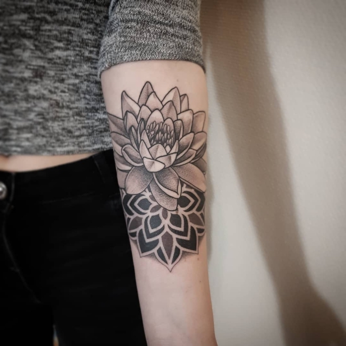 lotusblume bedeutung, schwarz graue tätowierung am arm, tattoo mit lotus als motiv am unterarm