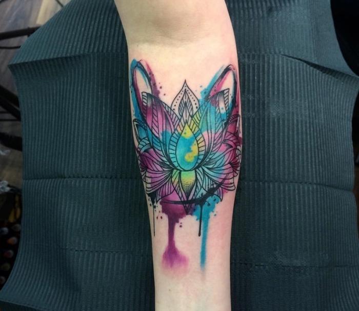 wasserfarben tattoo mit lotus als motiv, lotusblüte bedeutung, farbige tätowierung am unterarm