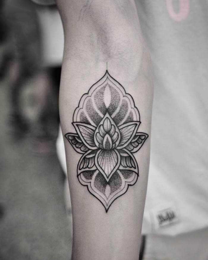 blumen tattoo in schwarz und grau, lotusblüte bedeutung und designs, blackwork tätowierung am unterarm
