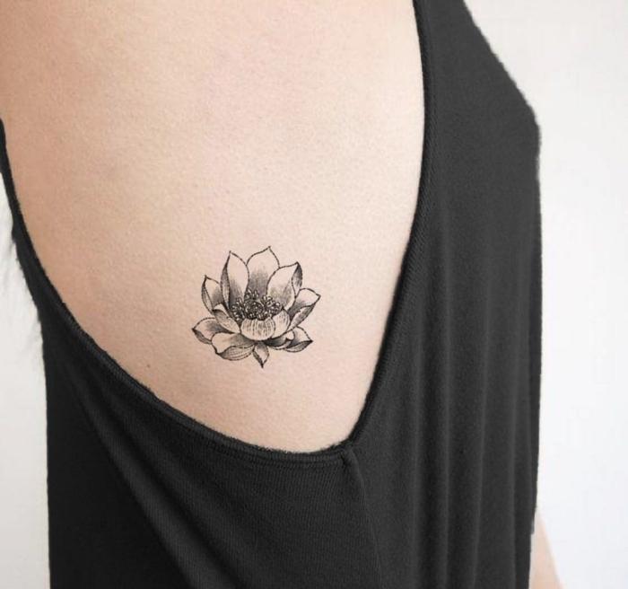lotusblume tattoo an der körperseite, frau mit kleiner tätowierung in schwarz und grau, blume