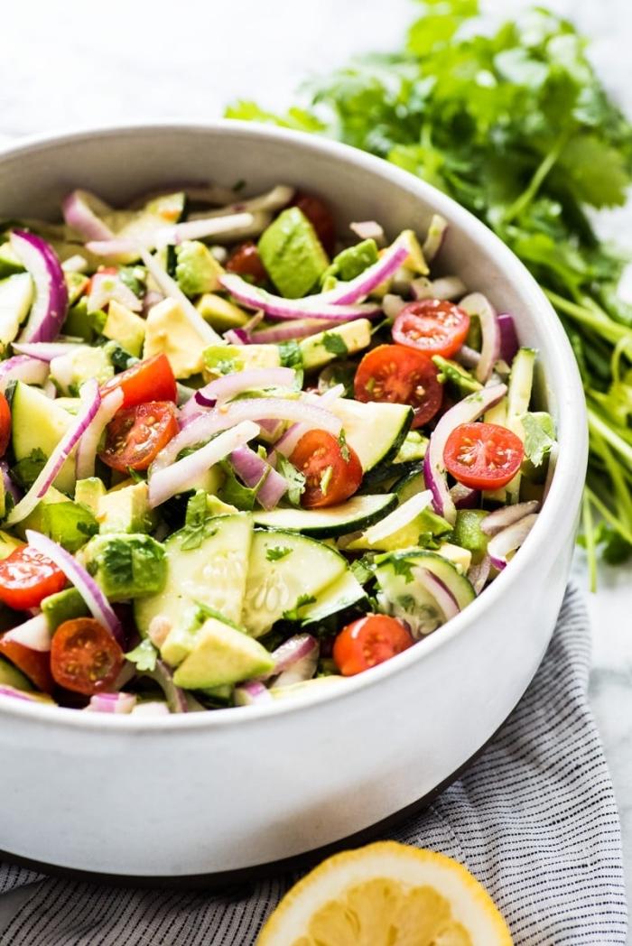 low carb rezepte abend, gesunder salat mit cherry tomaten, zucchini und zwiebel garniert mit zitronen