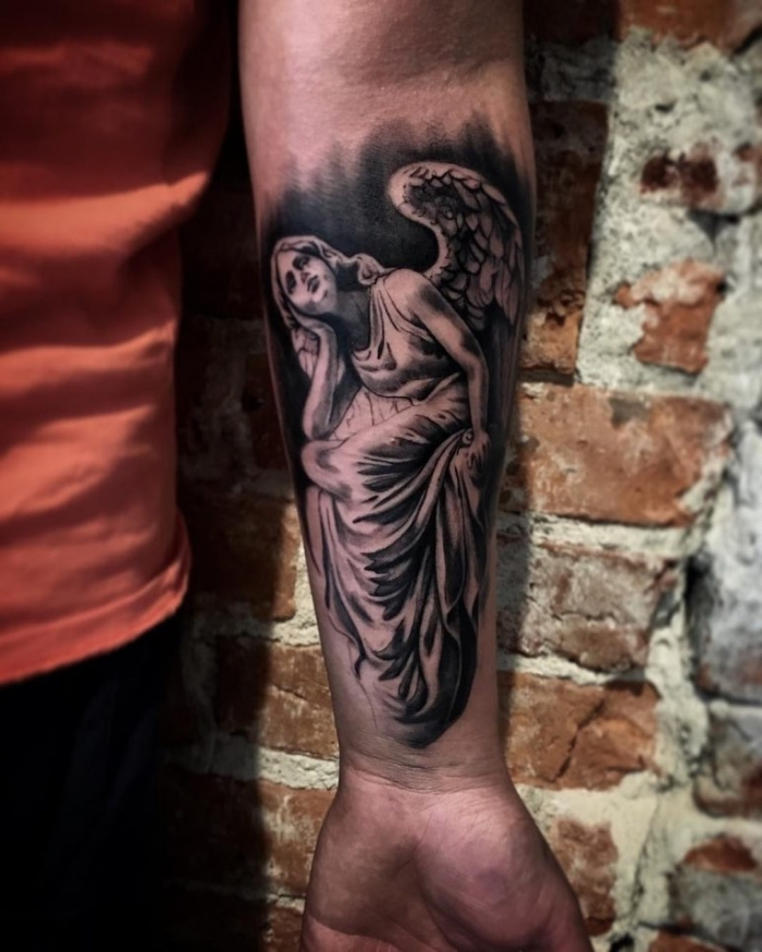 mann mit realistic tattoo am unterarm, frau mit engelsflügeln, schwarz graue tätowierung am unterarm