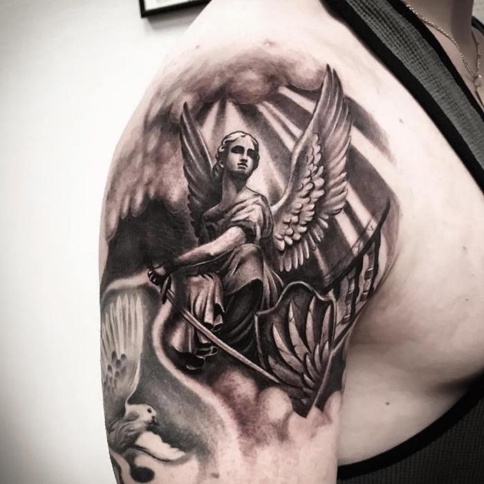 mann mit realitischem schutzengel tattoo am schulter, frau mit flügeln und schwert, sonnenschein
