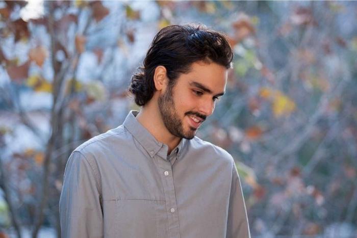 frisuren herren, ein zufriedener mann mit langen haaren bis zum neck, dunkle haare, bart