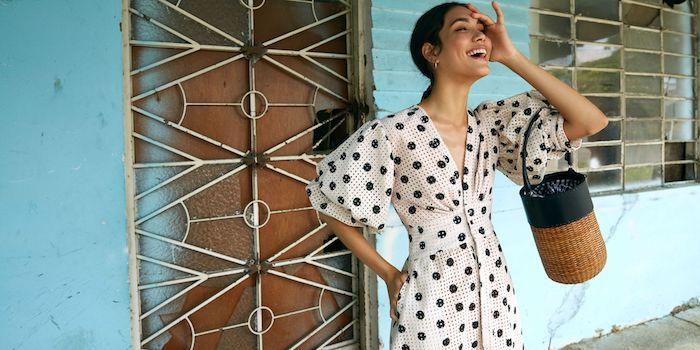 Modetendenzen Sommer 2019, weißes elegantes Kleid mit weiten Ärmeln, schwarze Punkte auf weißem Grund, Rattan Tasche