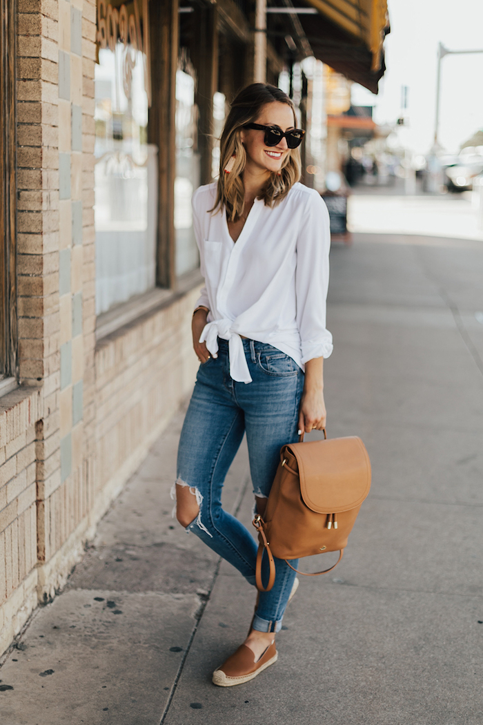 Weißes Hemd mit langen Ärmeln, zerrissene Jeans, brauner Lederrucksack