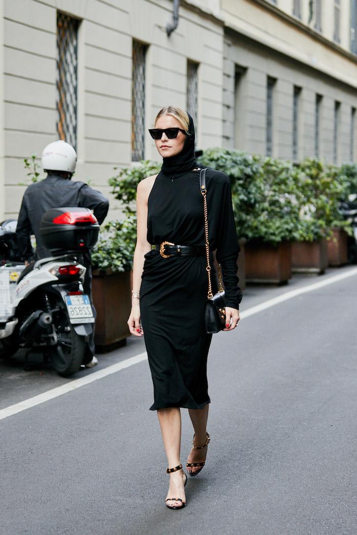 Sommermode 2019, schwarzes enges Kleid mit einem Ärmel und Kapuze, schwarze Pumps