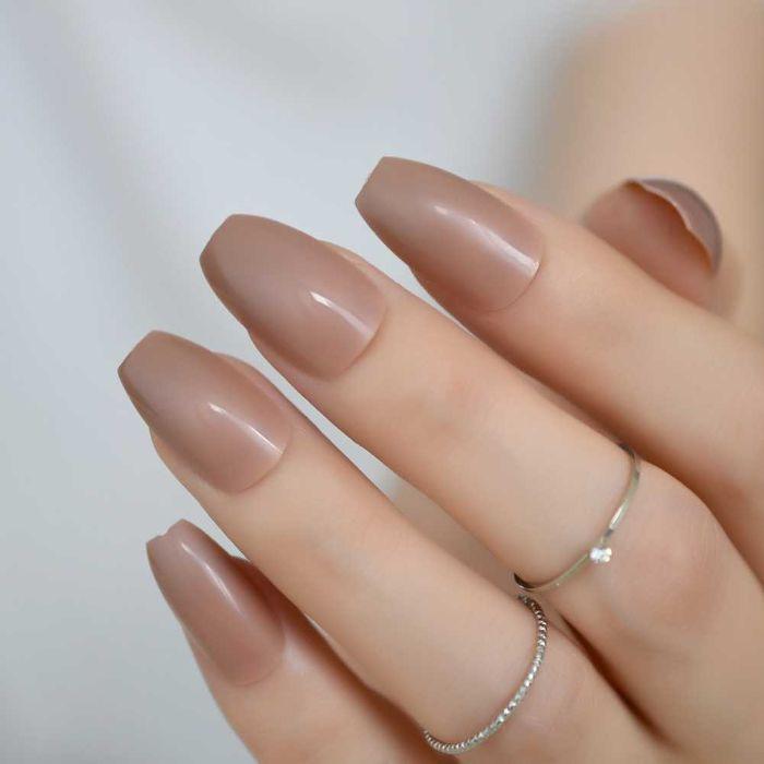 gelnägel spitz, beige maniküre, eine hand mit zwei kleinen ringen, beiges gellack