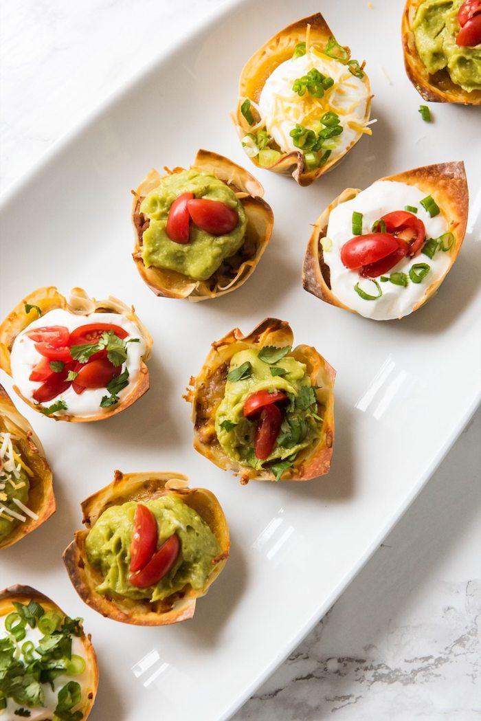 Kleine Häppchen aus Blätterteig mit Avocado und Cherry Tomaten, leckeres Fingerfood