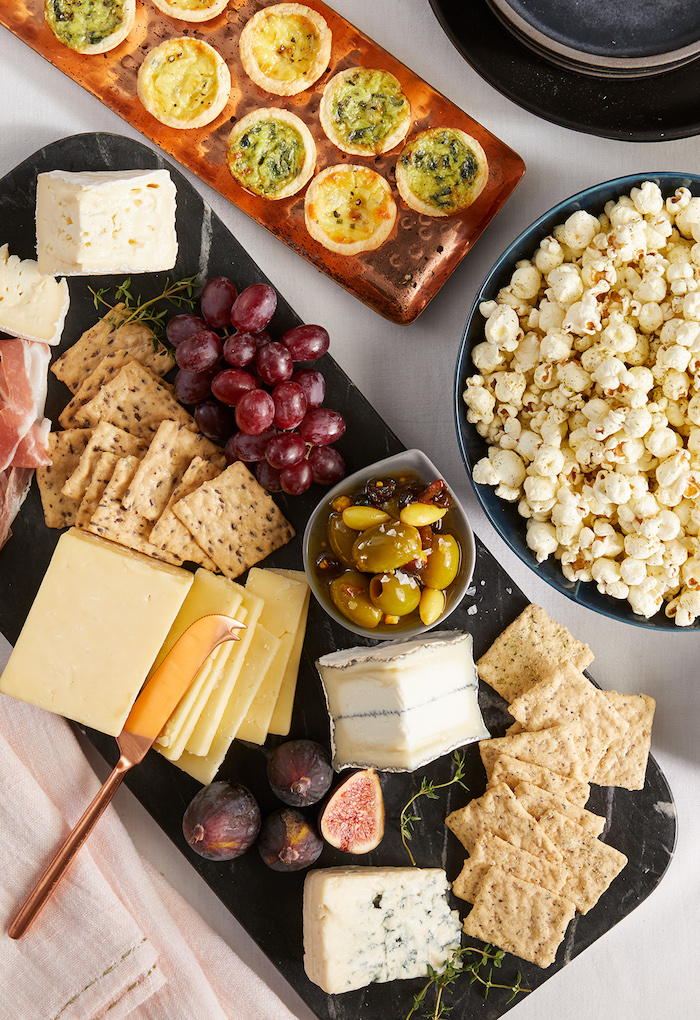 Party Essen Ideen, unterschiedliche Käsesorten und Kräcker, Trauben und Feigen, Schüssel voll mit Popcorn