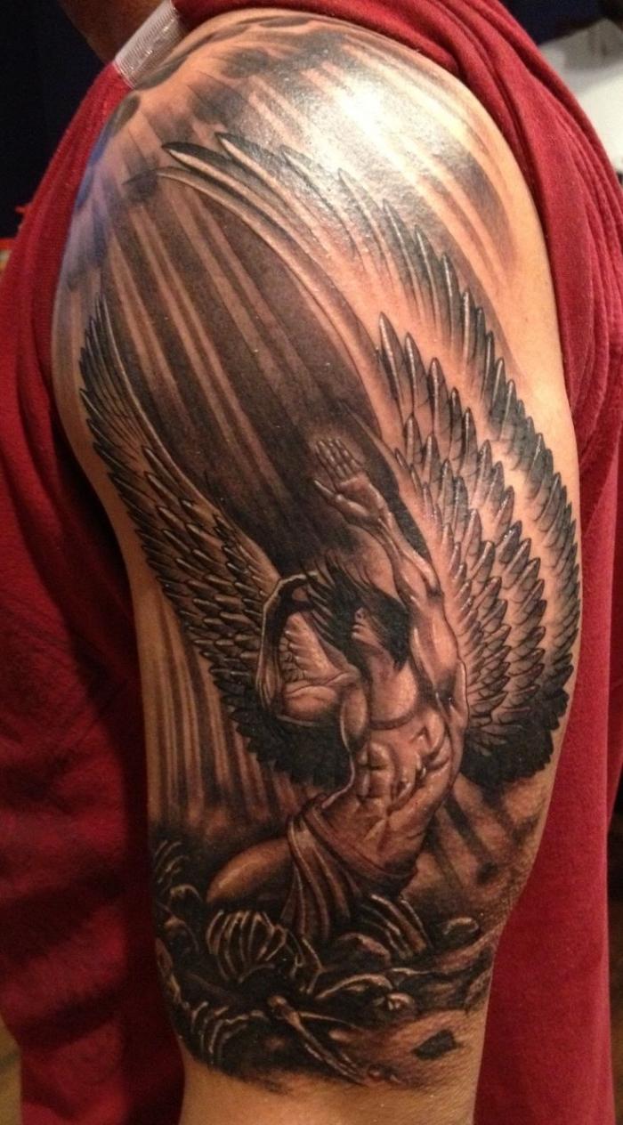 tattoo foto, realistic tattoo am aberarm, gefallener engel, schwarz graue tätowierung am oberarm