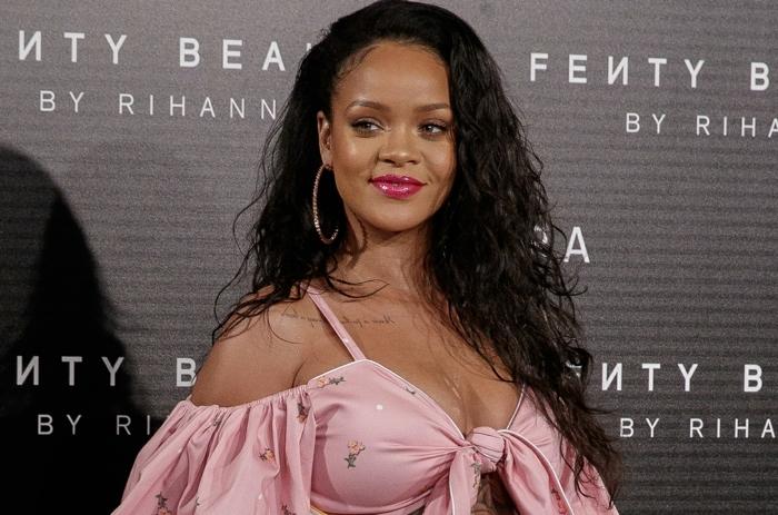 Rihanna mit einem rosa Kleid mit bunten Bildchen versehen, lange lockige Haare und enorme Ohrringe