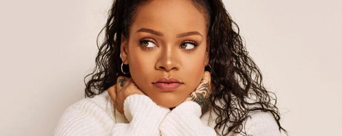Rihanna mit einem weißen Pullover, lange, schwarze lockige Haare und dezentes Make-up