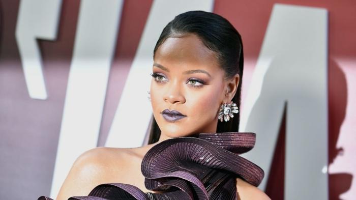 Rihanna mit glatten, langen, schwarzen Haaren und ein blauer Lippenstift, ein schwarzes Kleid