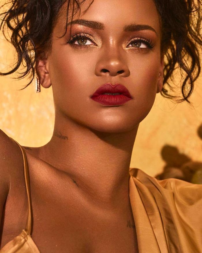 Rihanna mit glänzender Haut, ein roter Lippenstift, goldene Bluse, sie hat viele Tattoos