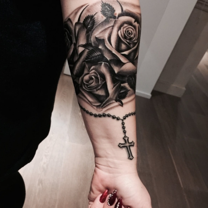 rosenkranz tattoo ideen, frau mit realitische schwarz grauer tätowierung am unterarm, drei rosen