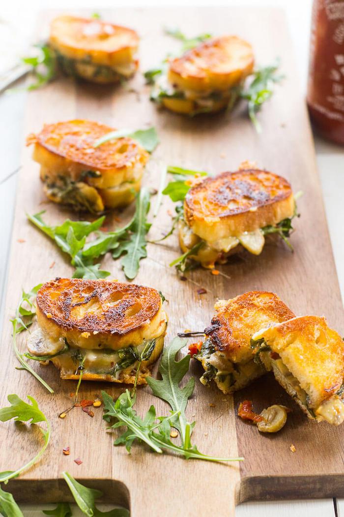 Kleine leckere Häppchen, gegrilltes Brot mit Käse und Rucola, Fingerfood schnell und einfach
