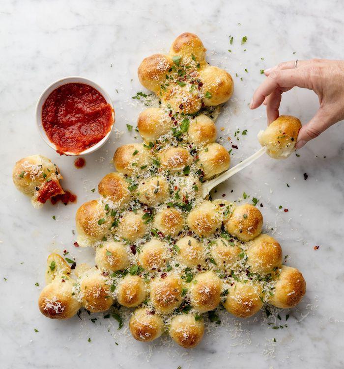 Party Essen für Weihnachten, Weihnachtsbaum aus kleinen leckeren Kugeln mit Käse, Tomatensoße in kleiner Schüssel
