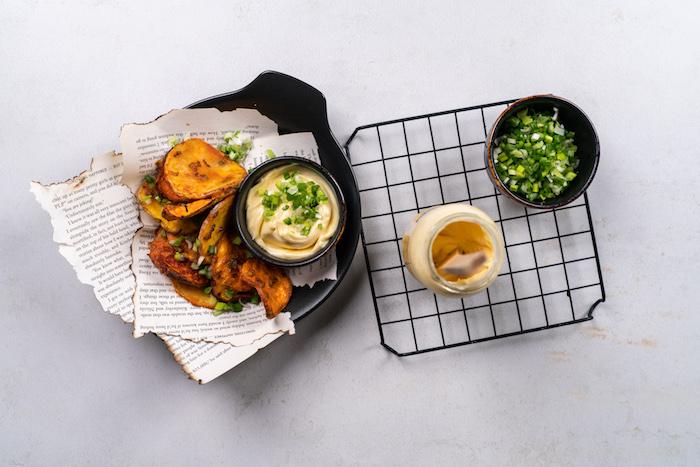 Kartoffelchips mit Dip aus Mayonnaise und Frühlingszwiebel servieren