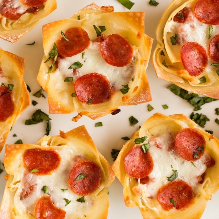 Mini Pizza aus Blätterteig mit Käse und Salami, kleine Snacks für Party, Fingerfood warm