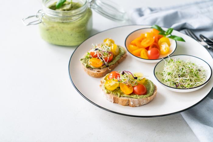 Avocado Pesto auf Brot mit Cherrytomaten und Sprossen, schnelle Brunch Idee