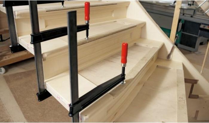 Treppen, rote und schwarze Schraubzwingen, eine Treppe aus Holz wurde gebaut